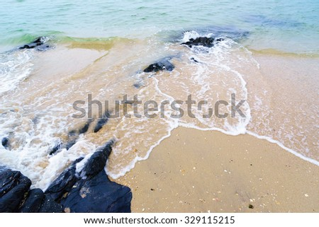 Yellow sand,green water and black stone:Blurred abstract background.
