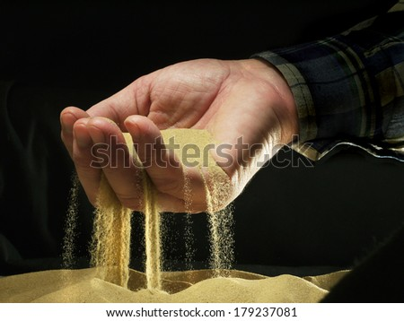 yellow sand strewed through fingers with the palm, dark background - stock photo