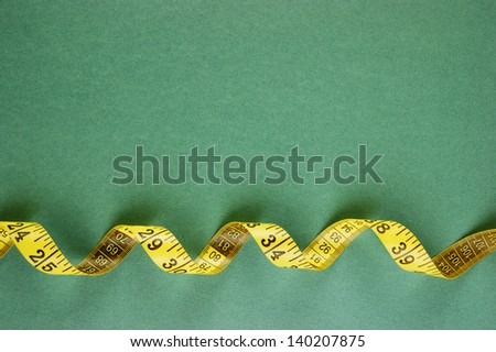 yellow sartorial meter on a green background - stock photo