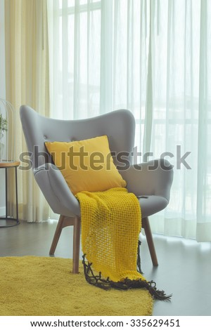 Yellow scarf and yellow pillow setting on gray color easy armchair in living room - stock photo