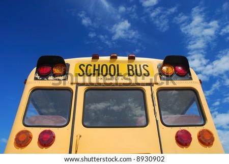 Yellow school bus against blue sky - stock photo