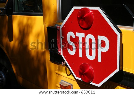 Yellow school bus and stop sign signalling all to pay attention to students crossing. - stock photo