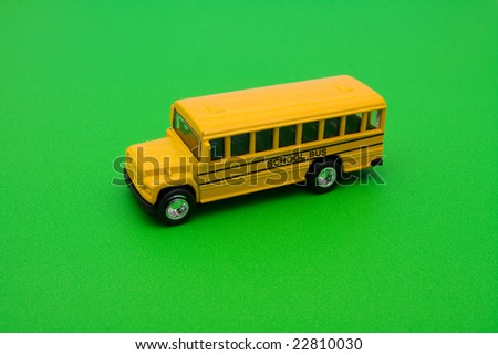 Yellow school bus sitting on green background, school bus - stock photo