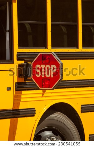Yellow school bus stop sign up close view. - stock photo