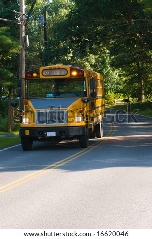 Yellow school bus stopped on country road, copy space at bottom - stock photo
