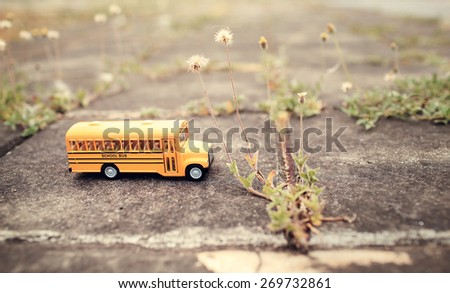 Yellow school bus toy model on country road.Vintage color style. - stock photo