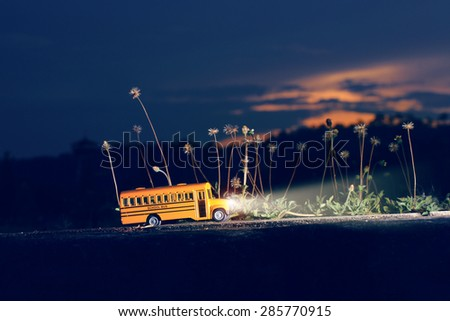 Yellow school bus toy model on twilight. - stock photo