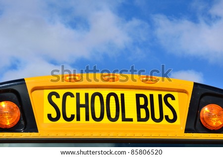 Yellow School Bus with Blue Sky and Clouds - stock photo