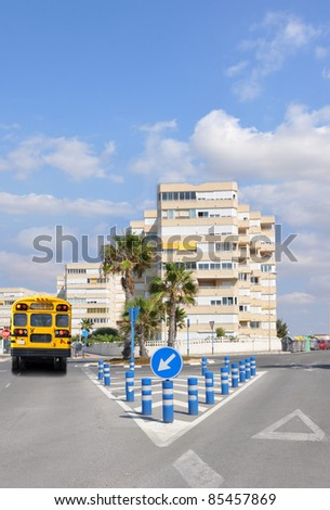 Yellow School Bus with Stop Sign Extended on Urban Street in Highrise Apartment Residential Area