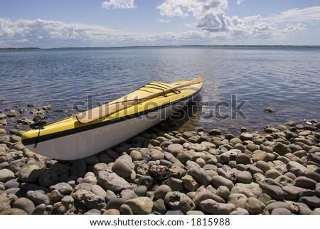 Yellow sea kyak on the rocky coast of Nissum bredning Jutland Denmark - stock photo