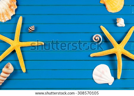 Yellow sea stars and few marine items on a blue wooden background.