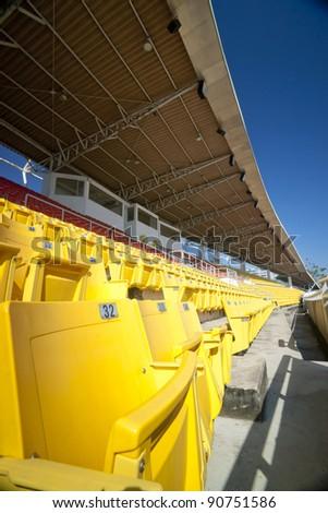 Yellow seat in velodrome stadium with blue sky - stock photo