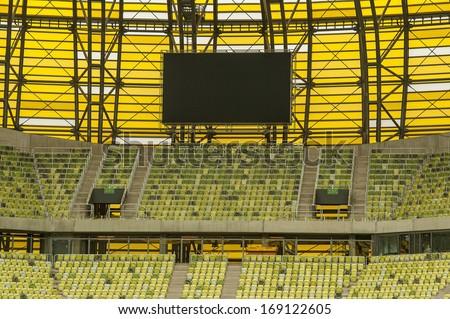 yellow seats and electronic billboard display at stadium - stock photo