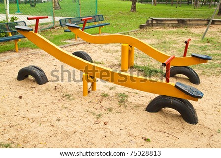 Yellow Seesaw in the Playground - stock photo