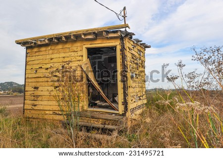 Yellow shed in a field with wires to the roof and a broken front door - stock photo