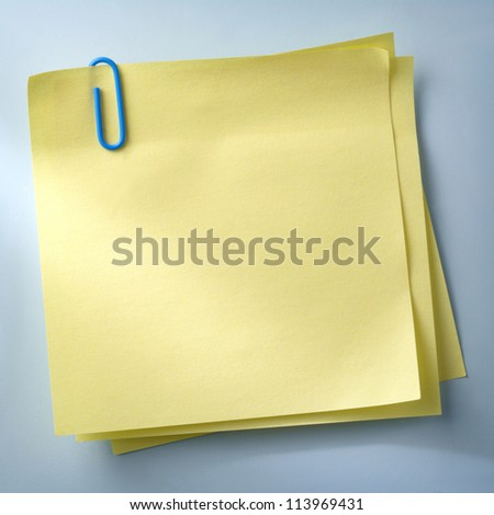 yellow sheet of paper for notes and paper clip - stock photo