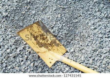 yellow shovel on the rock - stock photo