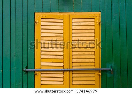Yellow shutters with a locker on a green plank wall. - stock photo