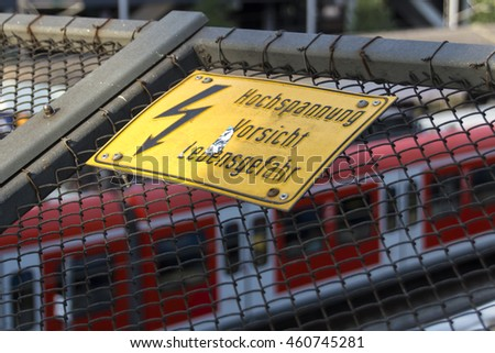 Yellow sign warning for high voltage contact wires above the rails, in the background is a red train of the Munich Sbahn - stock photo