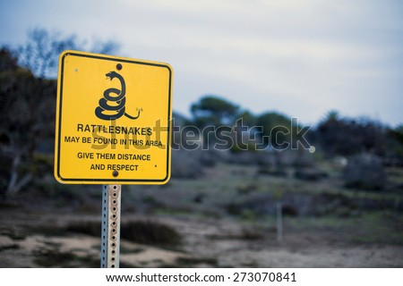 yellow sign with a warning for rattlesnakes - stock photo