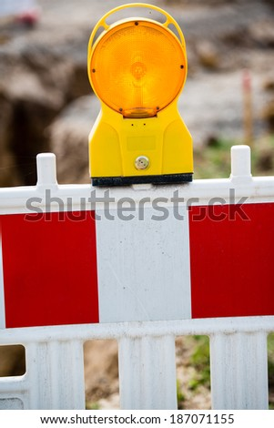 yellow signal lamp warning  against a building site with red and white barrier - stock photo