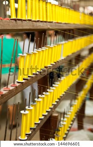 Yellow silk thread on wooden shelf - stock photo