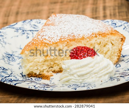 Yellow skillet cake with cream and strawberry - stock photo