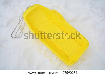 Yellow sled with snow - stock photo
