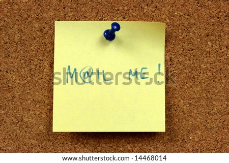 Yellow small sticky note on an office cork bulletin board. Electronic mail contact message.