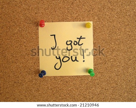 Yellow small sticky note on an office cork bulletin board. Surprise and striking message.