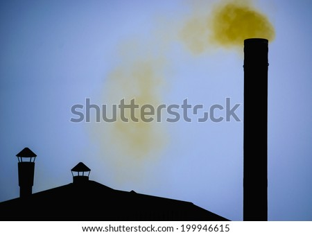 Yellow smoke from Silhouette of factory pipe over dark blue sky - stock photo