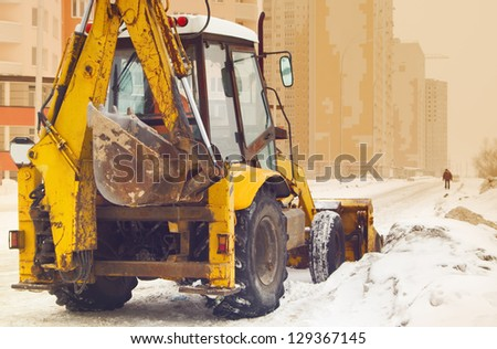 yellow snow plow on an empty street - stock photo