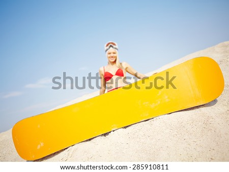 Yellow snowboard on sand with happy girl on background