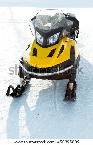 yellow snowmobile in snow
