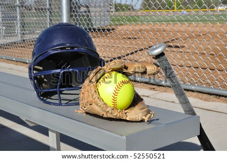 Yellow Softball, Helmet, Bat, and Glove on an Aluminum Bench - stock photo
