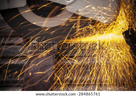 Yellow sparks at grinding steel material - stock photo