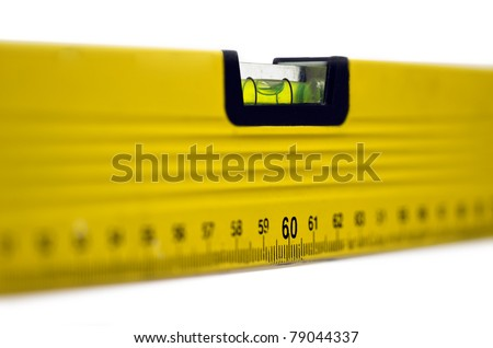 Yellow spirit level; well-used spirit level isolated against white ground; strong differential focus - stock photo