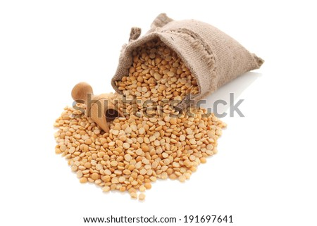 yellow split peas in a burlap bag with an wood scoop on a white background
