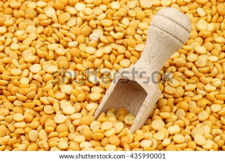 yellow split peas with wooden scoop background - stock photo