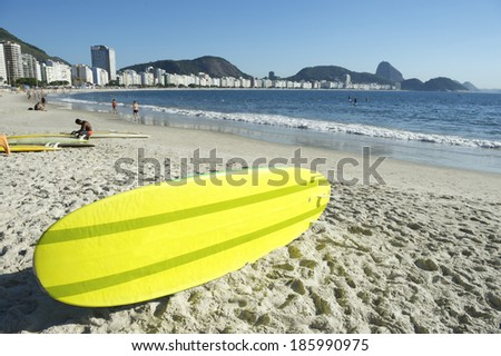 Yellow stand up paddle long board surfboard on Copacabana Beach Rio de Janeiro Brazil - stock photo