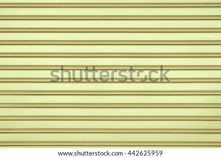 Yellow steel door with horizontal lines background. - stock photo