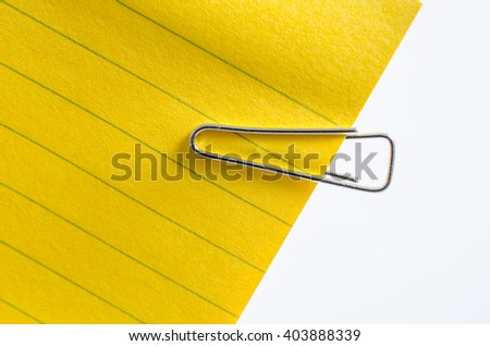 Yellow sticker and steel paper clip on white background.