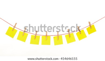 Yellow stickies hanged on red rope isolated on white
