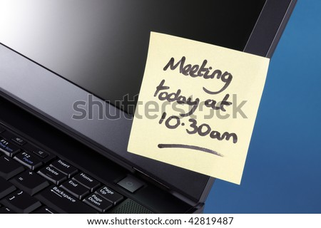 Yellow sticky note on a laptop computer reminding of a meeting today - stock photo
