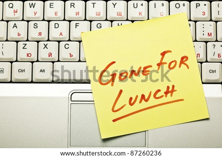 Yellow sticky note on a laptop keyboard with 'Gone for Lunch' on it. - stock photo