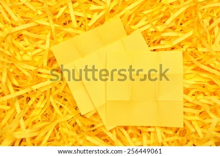 Yellow sticky note on shredded paper - stock photo