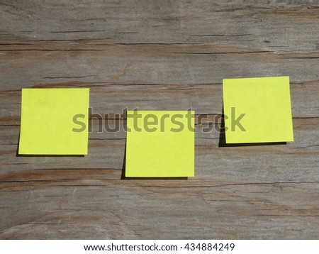Yellow sticky note papers on wooden background  - stock photo