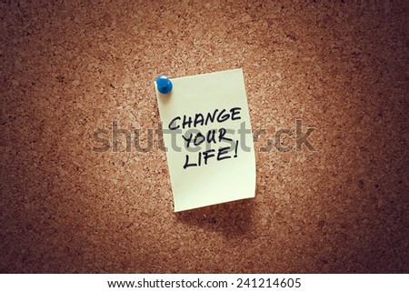 yellow sticky reminder note with change your life message on corkboard. - stock photo