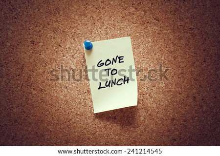 yellow sticky reminder note with gone to lunch message on corkboard. - stock photo