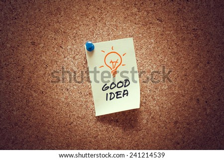 yellow sticky reminder note with good idea message and lit bulb illustration on corkboard.  - stock photo